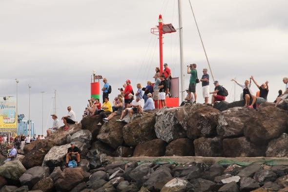 uitzwaaiers en fotografen op het havenhoofd